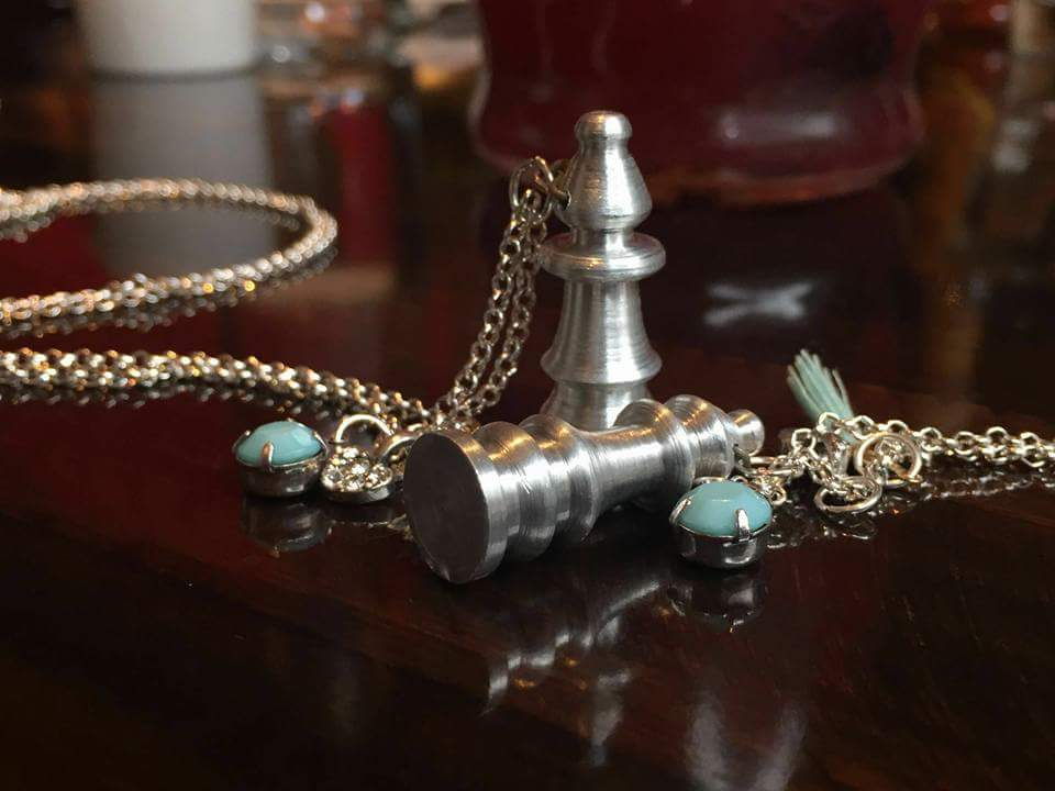 two metal turned chess pieces attahced to a chain and some charms to make them pendants.